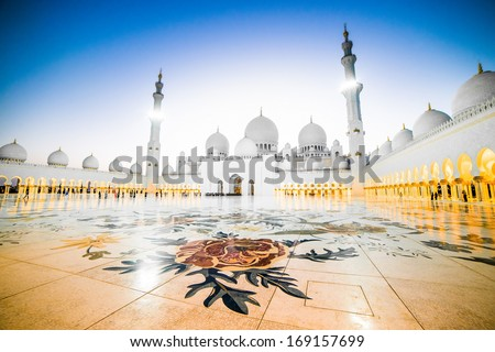 The courtyard of Sheikh Zayed Grand Mosque in Abu Dhabi with two minarets - stock photo