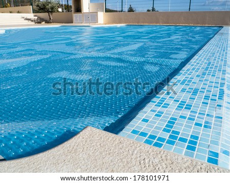 The cover of swimming pool  which also lets the pool heat up from the sun. - stock photo