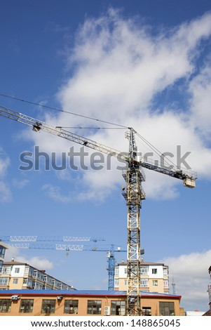 The crane machine at construction site on white clouds blue sky