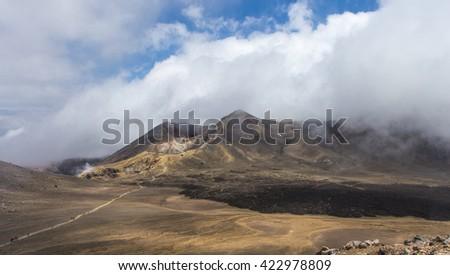 The crater of Tongariro volcano peeking through the clouds. North Island, New Zealand - 27/DEC/2014 - stock photo