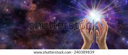 The Creative Spark - Female hands reaching up to a white burst of light on a wide deep space background with plenty of copy space on left hand side - stock photo