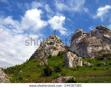 The cross on the background of clear sky at the top Biaklo (or Maly Giewont) near Olsztyn near Czestochowa in Poland - stock photo