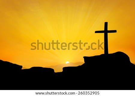 The cross on top a mountain at sunset - stock photo