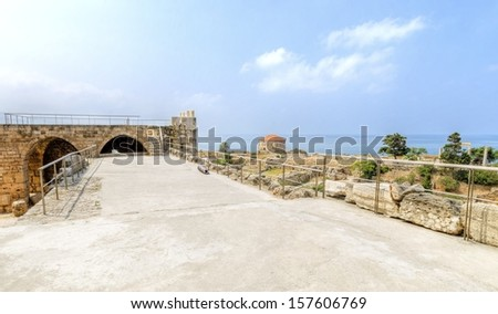 The crusaders' castle in the historic city of Byblos, Lebanon.A view of the ancient site,the top of the castle,battlement,the traditional lebanese house and the pillars of the roman colonnaded street. - stock photo