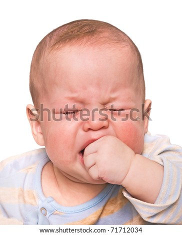 The crying boy in tears, hand in mouth, on the white background