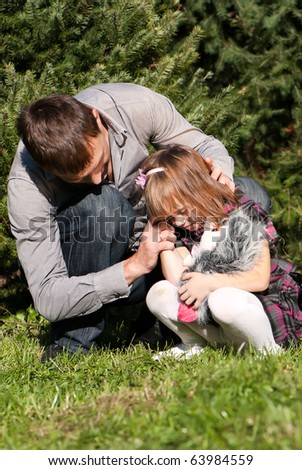 The crying little girl with the father in park