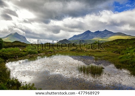 The Cuillin Hills of Isle of Skye reflected in a loch on a stormy day.