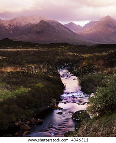 The Cullin Mountains, Shrouded in storm clouds at dusk. A Mountain Stream cascades in the foreground - stock photo