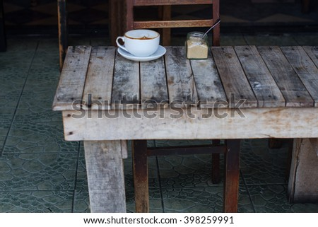 The cup of coffee costing on a wooden little table, a cappuccino, coffee with milk, fragrant a cappuccino - stock photo