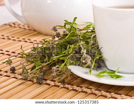 the cup of herbal tea with thyme on bamboo mat background