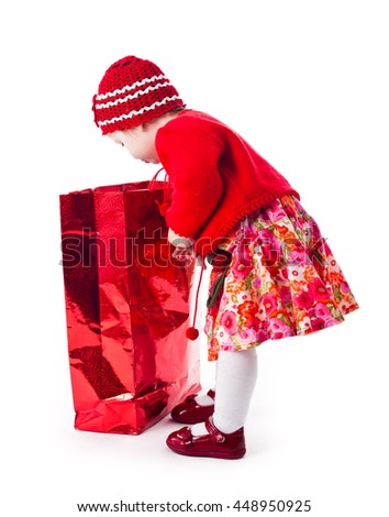 The curious little girl in the red dress looks in the red shopping bag isolated on white - stock photo