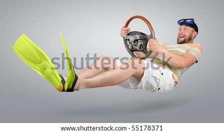 The curious man in green flippers and shorts with a wheel racing - stock photo
