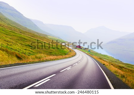 The curve of the road in the mountains to the ocean. The Faroe Islands. - stock photo