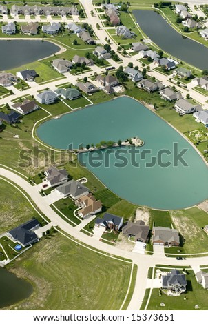 The curving streets of a suburban housing development surround a small blue pond, as seen from the air.