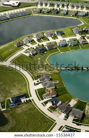 The curving streets of a suburban housing development surround a small blue pond, as seen from the air. - stock photo