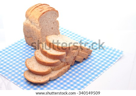 The cut loaf of bread on mat - stock photo