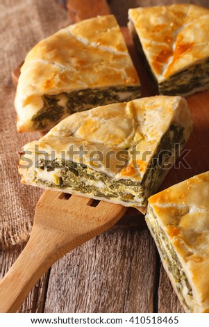 The cut pie spanakopita close-up on the table. vertical