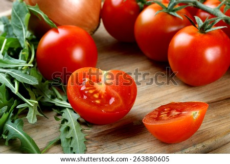 The cut tomatoes and green salad - stock photo