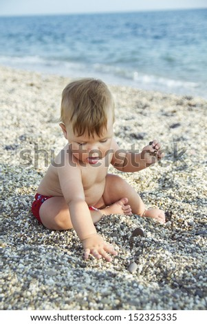 The cute baby boy playing on the beach. Little boy on the sand. Sea and seashore as background.