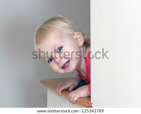 The cute baby girl peeping out from behind the wall - stock photo
