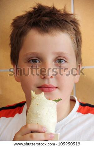 The cute boy eating wrap sandwich - stock photo
