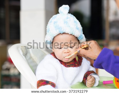 the cute boy is eating some food by spoon