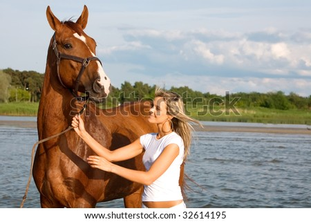 The cute girl with a horse on seacoast - stock photo