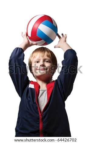 The cute little boy in a jumpsuit holds a volleyball ball over head and smiles. Isolated over white background. - stock photo