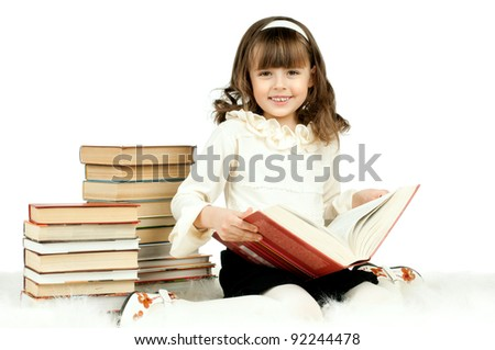 the cute little girl lie with textbook and happy smile, on white background, isolated - stock photo