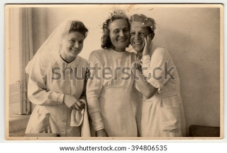 THE CZECHOSLOVAK  REPUBLIC - CIRCA 1930s: Vintage photo shows nurses, one of them prepares to wedding ceremony . Black & white antique photography.