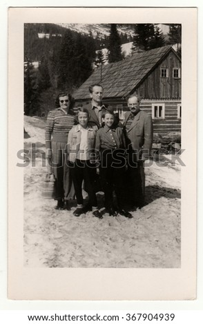 THE CZECHOSLOVAK  SOCIALIST REPUBLIC, CIRCA 1950: A vintage photo shows group of people In front of a log house in winter, circa 1950s.