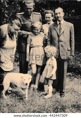 THE CZECHOSLOVAK SOCIALIST REPUBLIC - CIRCA 1960s: Retro photo shows family and dog outside. Black & white vintage photography - stock photo