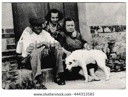 THE CZECHOSLOVAK SOCIALIST REPUBLIC - CIRCA 1960s: Retro photo shows rural people sit on a doorstep with dog. Black & white vintage photography