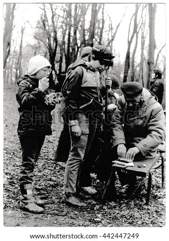 THE CZECHOSLOVAK SOCIALIST REPUBLIC - CIRCA 1980s: Retro photo shows young tourists and their chief in the forest. Black & white vintage photography