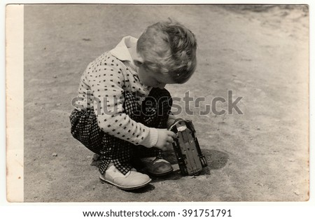THE CZECHOSLOVAK SOCIALIST REPUBLIC - CIRCA 1960s: Vintage photo shows boy plays with toy car outdoors. Antique black & white photography. - stock photo