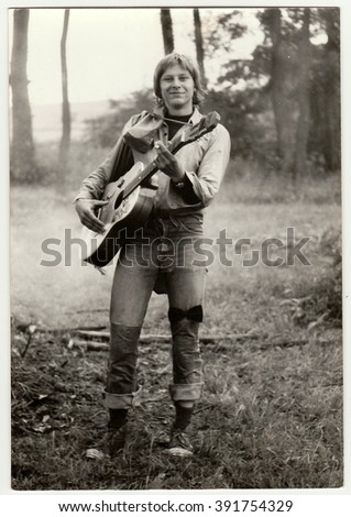 THE CZECHOSLOVAK SOCIALIST REPUBLIC - CIRCA 1980s: Vintage photo shows young hiker plays the guitar outdoors. Antique black & white photo.