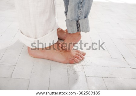 The daddy's and his nine months old son feet , small and big  on white home background - stock photo