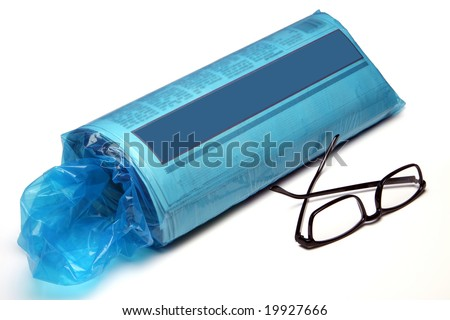 The daily newspaper in the blue plastic bag fresh from the driveway.  The bag is torn and dirty.  The paper shows a blue banner for your own text!  A pair of black reading glasses lies in front.  I - stock photo
