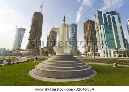 The Dallah coffee pot sculpture on the Corniche in Doha the capital of Qatar, behind it are the new high rise building being built to fill the skyline. - stock photo