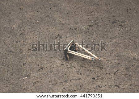 The damaged old metal chair left out and stuck in mud - stock photo