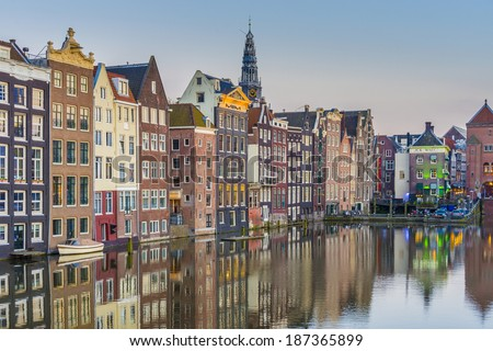 The Damrak canal, running between Amsterdam Centraal in the north and Dam Square in the south in Amsterdam, Netherlands. - stock photo