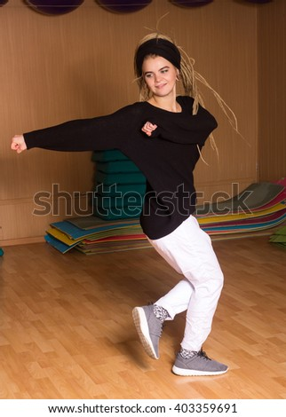 The dancer in white pants and bandana is in movement in the dance studio