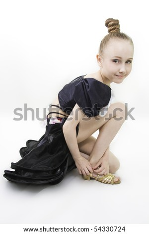 The dancing girl has sat down to clasp a shoe to a white background - stock photo