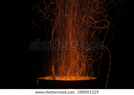 The dancing sparks from a fire on a black background. - stock photo
