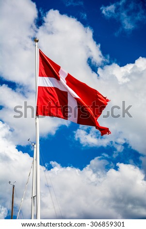 The danish flag and blue and cloudy sky  - stock photo