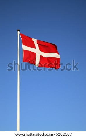 The Danish flag, Dannebrog, against a blue sky - stock photo