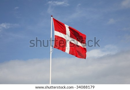 The Danish flag, Dannebrog against white clouds and a blue sky. - stock photo