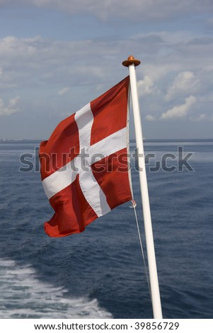 The danish flag waving at the sea. - stock photo