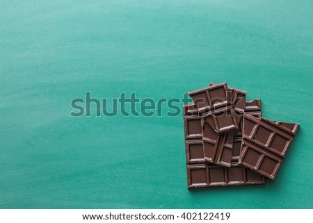 the dark chocolate bars on chalkboard - stock photo