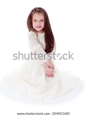 The dark-haired girl in a beautiful bright dress.Happiness concept,happy childhood